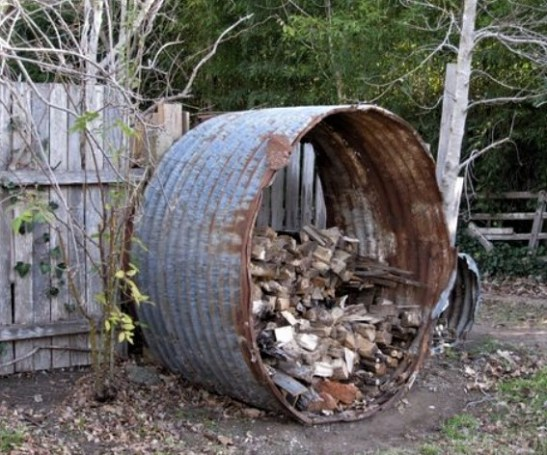 An old tank shelters a woodheap.