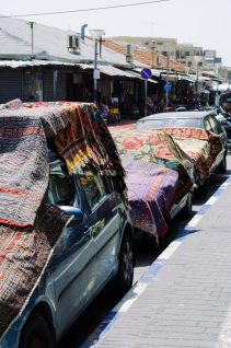 This seems to be some sort of car shade/display area exchange between the carpet merchants and the car owners.