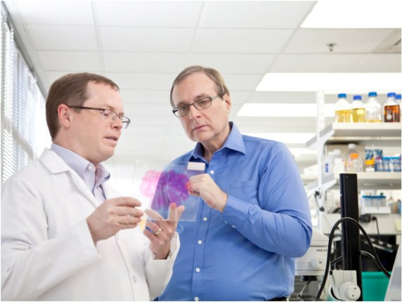 Paul G. Allen studies a brain sample with Allen Institute for Brain Science CEO Allan Jones.