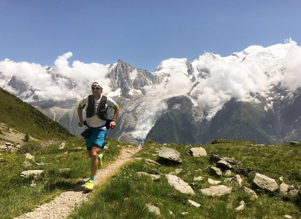 Man running up a hill with mountains in the background