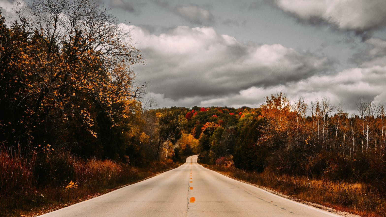 Road leading towards cloudy skies