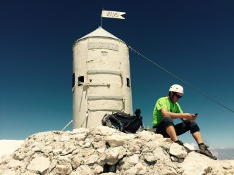 Summit of Triglav with modern mountaineer