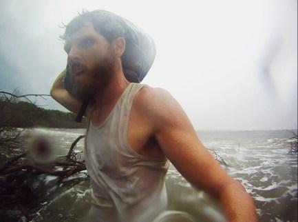 Paul Ferguson walking bag along Ararapira beach, Brazil