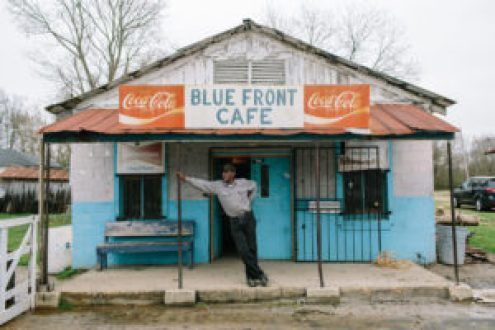 """Bentonia, MS - 3/11/2015 - Jimmy """"Duck"""" Holmes stands on the front porch of The Blue Front Cafe. The Blue Front Cafe opened in 1948 under the ownership of Carey and Mary Holmes, an African American couple from Bentonia. In its heyday the Blue Front was famed for its buffalo fish, blues, and moonshine whiskey. Jimmy """"Duck"""" holmes took over the cafe from his parents in 1970 and has continued to operate it as an informal, down-home blues venue that has gained international fame among blues enthusiasts."""