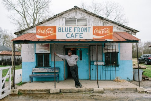 "Bentonia, MS - 3/11/2015 - Jimmy ""Duck"" Holmes stands on the front porch of The Blue Front Cafe. The Blue Front Cafe opened in 1948 under the ownership of Carey and Mary Holmes, an African American couple from Bentonia. In its heyday the Blue Front was famed for its buffalo fish, blues, and moonshine whiskey. Jimmy ""Duck"" holmes took over the cafe from his parents in 1970 and has continued to operate it as an informal, down-home blues venue that has gained international fame among blues enthusiasts."