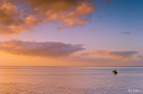 A fishing boat makes its way out to sea in the minutes just after sunrise. Kalk Bay, November 2009