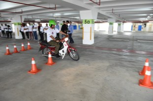 Participants maneuvering motorcycle at JPJ booth during the Petron Road Safety Amazing Race Challenge