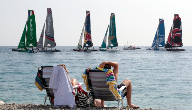 "People on the beach take advantage of warm weather to sit and watch the ""Extreme Sailing Series"" regatta on the Promenade Des Anglais in Nice"