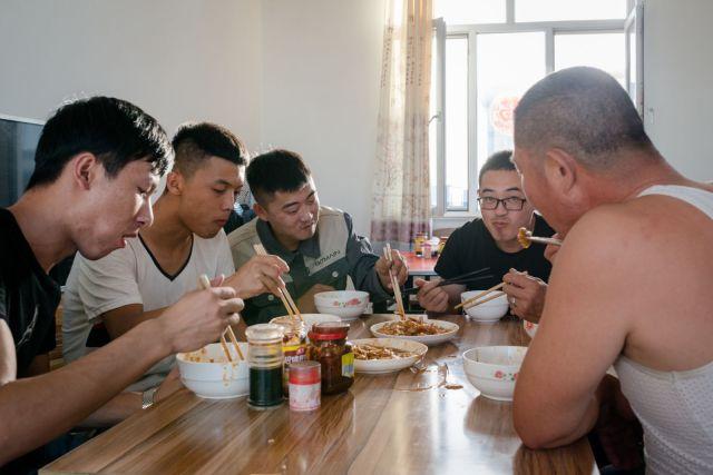 Radnici za stolom rudarske trpezarije uživaju u obedu