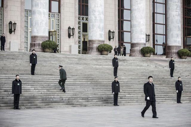 Poslanik se penje uz stepenice između čuvara pred Velikim domom naroda uoči 5. zasedanja 12. kongresa naroda i narodnosti u Pekingu 5. marta (Qilai Shen/Bloomberg)