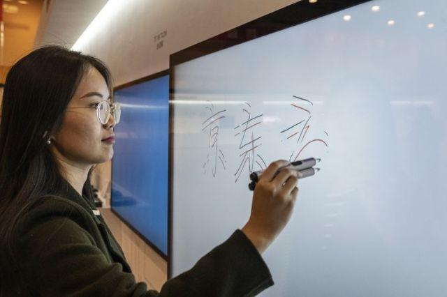 Zaposleni izvlači BOE ekran kako bi pokazao svoju multi-touch funkciju. Foto: Gilles Sabrie/ Bloomberg