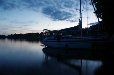 wieczorem nad jeziorem niegocin na terenie pola namiotowego i przystani leśna keja w bogaczewie na mazurach, widoczny jacht
