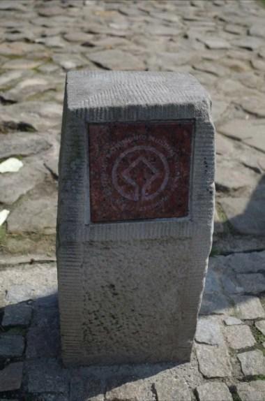 kamienny pachołek z symbolem wpisania na listę unesco zabytkowego drewnianego kościółka w lipnicy murowanej