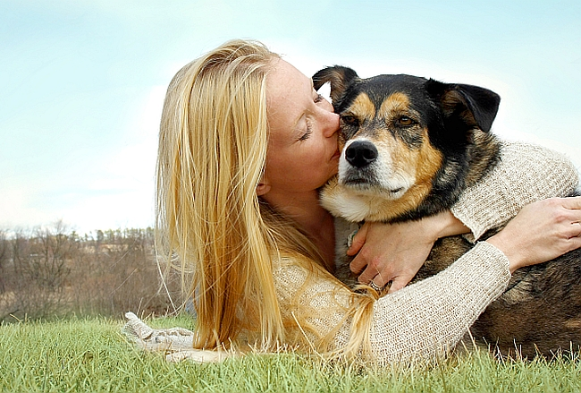 Young Woman Kissing German Shepherd Dog Outside