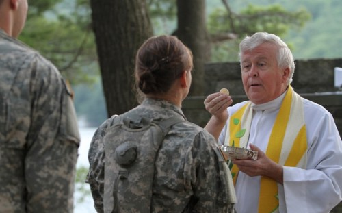 Augustinian Fr. Edson Wood, brigade chaplain at the U.S. Military Academy, distributes Communion during Mass at Camp Buckner in West Point, N.Y., in 2011. (CNS/Gregory A. Shemitz)