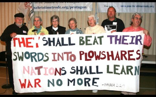 Seven plowshares activists seen together at the Pax Christi Metro DC-Baltimore Peacemaker of the Year event. They are holding a sign created by the late Philip Berrigan, who participated in the first action in 1980. Photo by Ted Majdosz