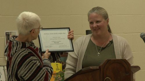"""Kathy O'Leary of Pax Christi New Jersey accepting a certificate from New Jersey Peace Action recognizing the Shrine of St. Joseph as an official """"peace site."""""""