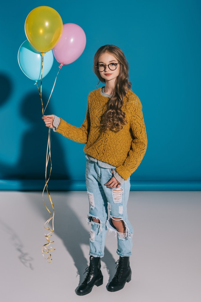 Teenage girl with long hair and glasses in a sweater holding balloons