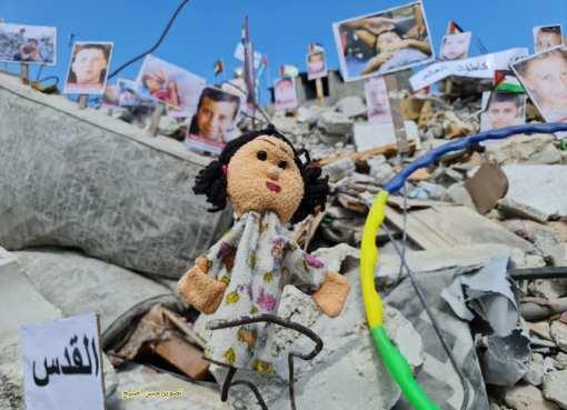 شاهد: معرض صور لشهداء غزة الأطفال والنساء على ركام المنازل التي دمرها عدوان الاحتلال الأخير
