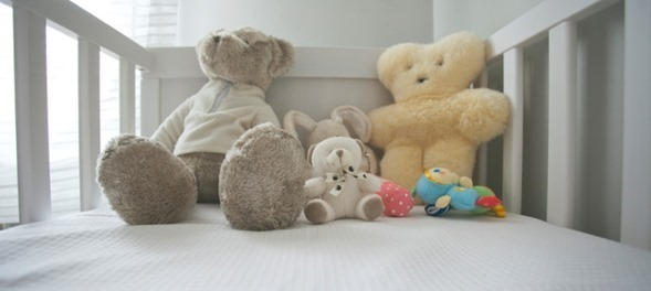 A cute crib of a baby with variety of teddies.