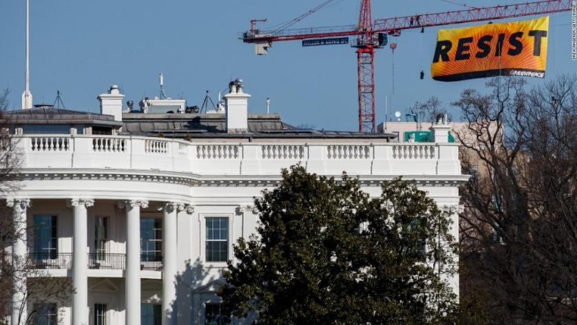 Activists unfurl 'resist' banner after climbing construction crane near the White House