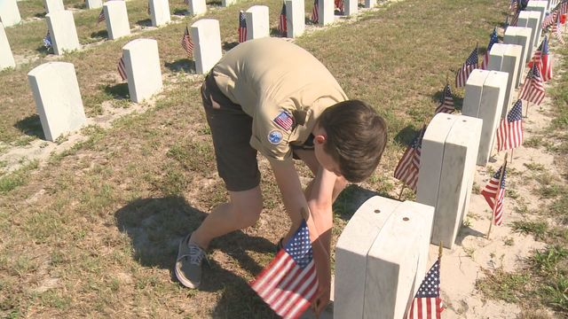 Local scouts place flags on gravesites