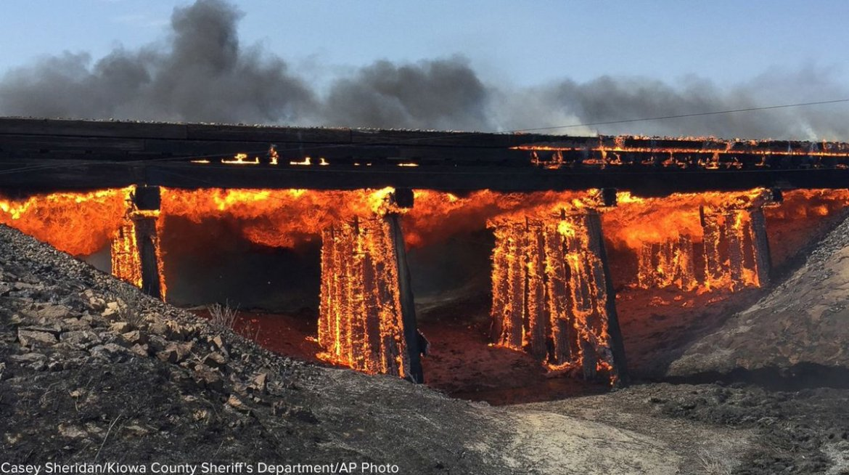 Colorado sheriff captures dramaticimage of grassfire engulfing abandoned railroad trestle.