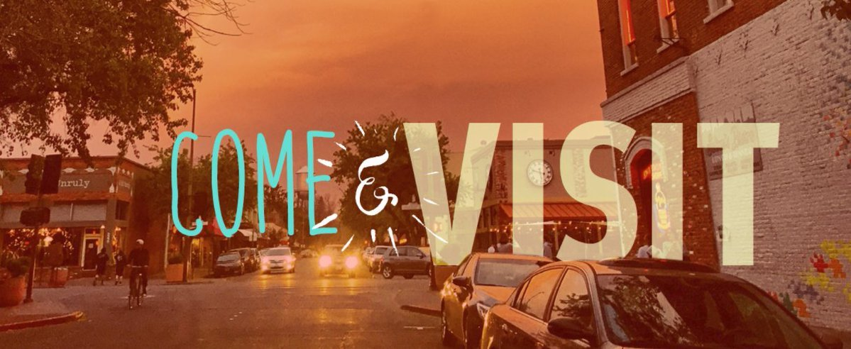 """""""Come and visit"""" superimposed over a dusk picture of downtown Chico."""