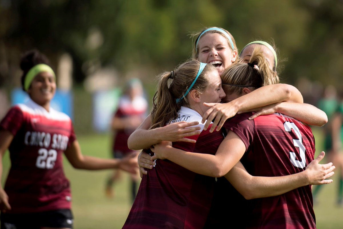 Chico State women's soccer players celebrate with a group hug.