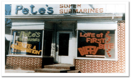 A picture of the first Subway sandwich store. The sign is blue and says: Pete's Super Submarines. The fascade is brick and there are windows that cover both of the walls. The door is in the middle. The whole place looks very small. There are brick steps leading up to the door.