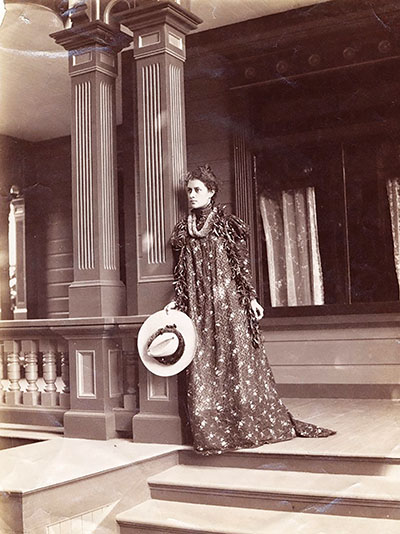 Princess Ka'iulani standing on top of steps on the porch of her house at 'Āinahau; wearing the holokū and lei, 1898. public domain photo by Frank Davey