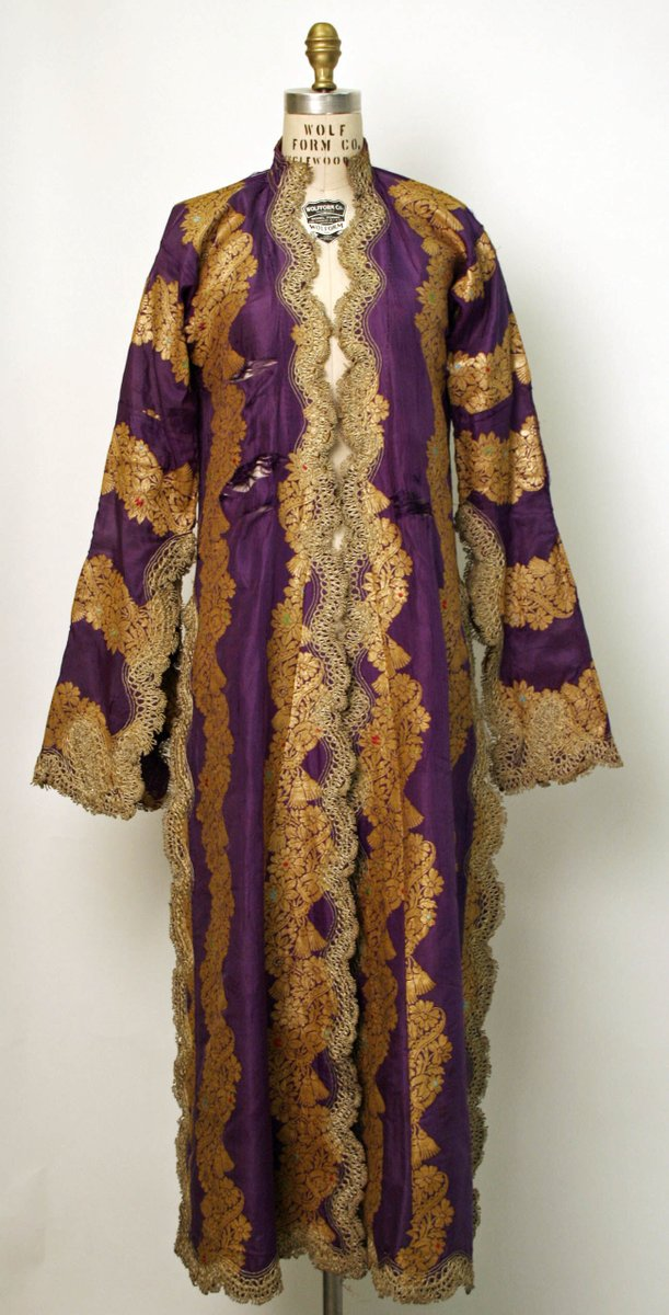 A kaftan from Turkey with embroidered edges on a purple striped background with orange accents. Met Museum.