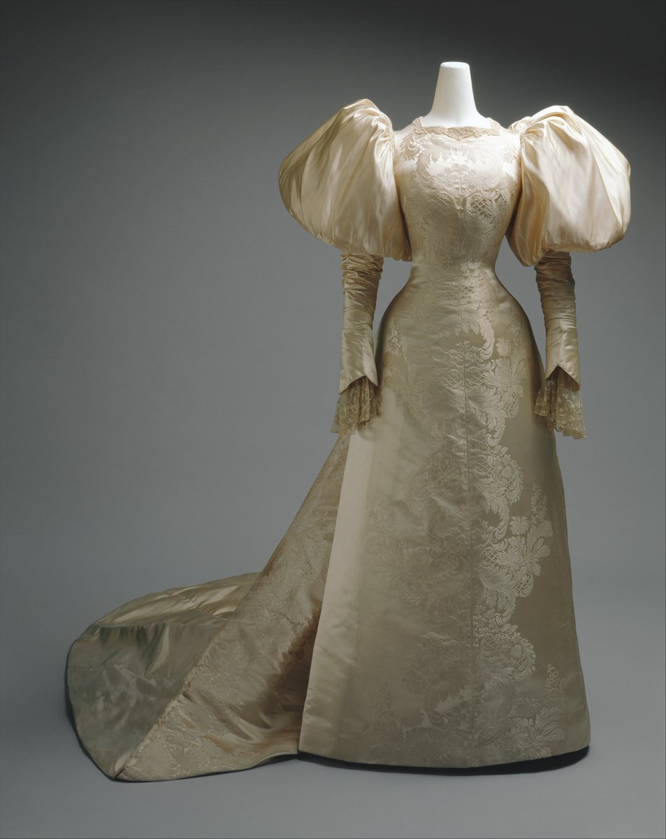 Employing a textile design that mirrors itself from selvage to selvage, this dress is pieced into a perfectly symmetrical image at the center front. Impeccable finishing details such as this distinguish the couture garment from the countless products of the ready-to-wear market that flourished in the mid- to late nineteenth century as a result of the Industrial Revolution. The use of the textile pattern to emphasize the woman's fashionable hourglass silhouette, achieved with the help of a steel-boned corset, further demonstrates the mastery of dressmaking technique at the House of Worth, as do the tiny handstitched cartridge pleats at the shoulder that create voluminous sleeves. The design of this sleeve, broad at the upper arm and fitted at the lower arm with the sleeve extending over the back of the hand, refers to sixteenth-century dress styles. - Met Museum, public domain