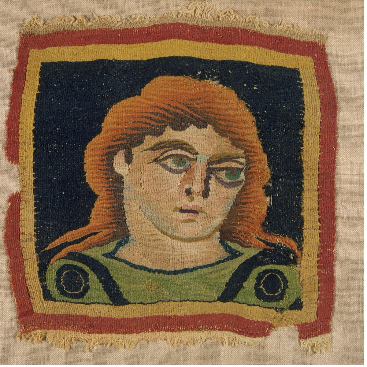 ©Victoria & Albert Museum, London - Square panel depicting a portrait bust of a young man, almost certainly of Adonis, probably to be appliquéd to a tunic or a furnishing textile. Tapestry-woven wool with small quantities of linen. Coloured wools make up the man's head and clothing and the background: his tunic is green with purple shoulder-bands and roundels; the background is dark purple; the border is red and yellow.