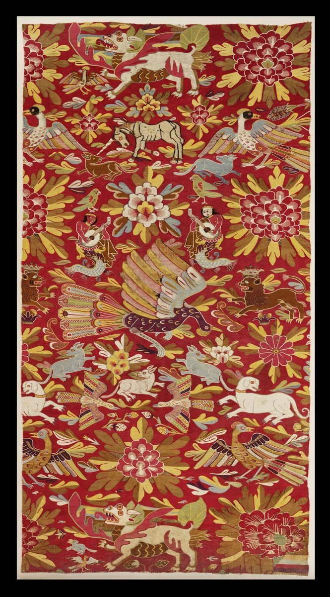 (c)Victoria and Albert Museum, London - A portion of a tapestry woven in coloured wools, silks and silver-gilt threads on cotton. The design depicts a variety of Asian-derived motifs of creatures and flowers against a red background.    At the centre of the design is a large bird with bright plumage, probably a phoenix depicted as being similar in appearance to a peacock. This bird is surrounded by flowers and leaves of differing shapes and sizes and also a number of stems bearing strawberries. Amidst these forms are numerous creatures: merpeople playing stringed instruments (suggestive of lutes); a crowned lion, parrots and other birds with multi-coloured plumage; a unicorn with its head lowered; dog-like animals, one of which wears a golden collar; and two mythical creatures with the appearance of stylised lions.