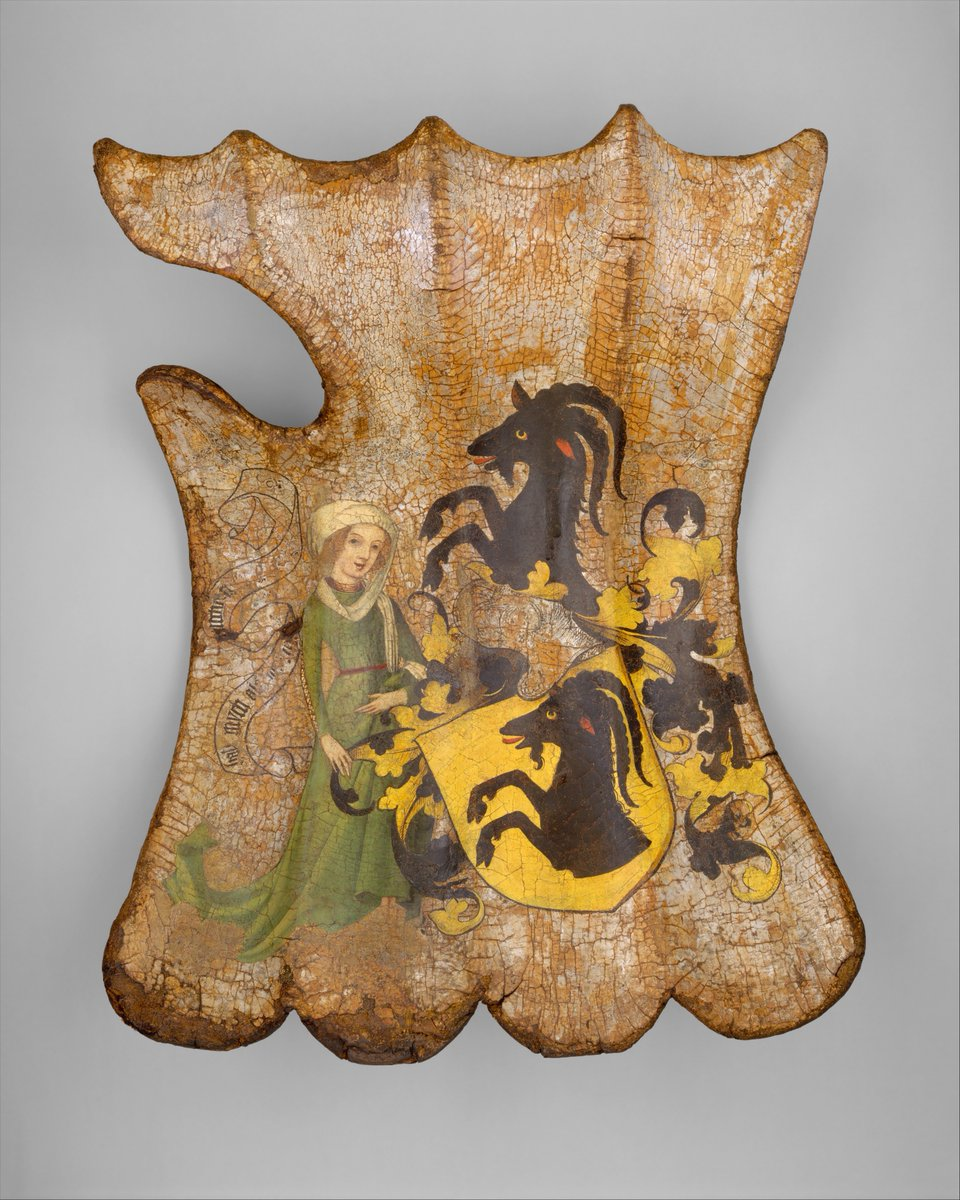 This shield is painted with a coat of arms belonging either to the Gottsmann family or to the related Türriegel family, both of Franconia. The female figure at the side holds a banderole inscribed in part with a motto in German: HAB MYCH ALS ICH BIN... (Take me as I am...). The decoration, with its brilliant colors on a silver-foil ground, is remarkably well preserved because it was hidden for centuries beneath layers of later paint. On the leather-lined back of the shield are traces of a painted figure of Saint Christopher, whose image was thought to protect against sudden death. - Met Museum, public domain.