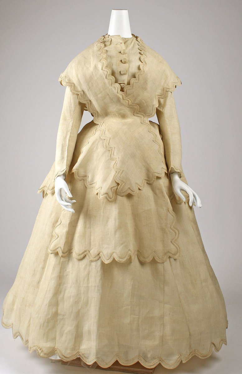 A beige, scalloped dress from 1870. It has a high collar, and long sleeves, and a criss-crossed stole that matches the rest of the dress. Large buttons. Very beige. Beige beige.