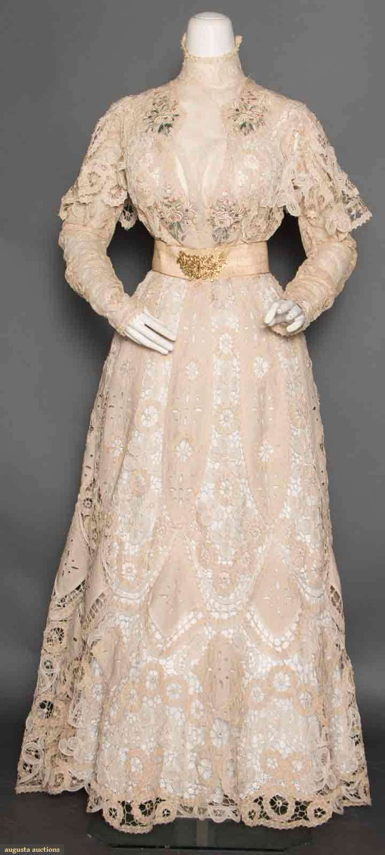 """2 piece cream Battenburg lace w/ cutwork linen insertions & pastel colored embroidered appliques on bodice, embroidered net lace plastron, sleeves & neckband, B 34""""-36"""", W 25"""", trained skirt L 39""""-45"""", (ribbon on belt torn, back hemline soiled, 4"""" tear in brides near hem, waistbands on bodice & skirt replaced) very good. Suddon-Cleaver Collection, Toronto. via Augusta Auctions"""