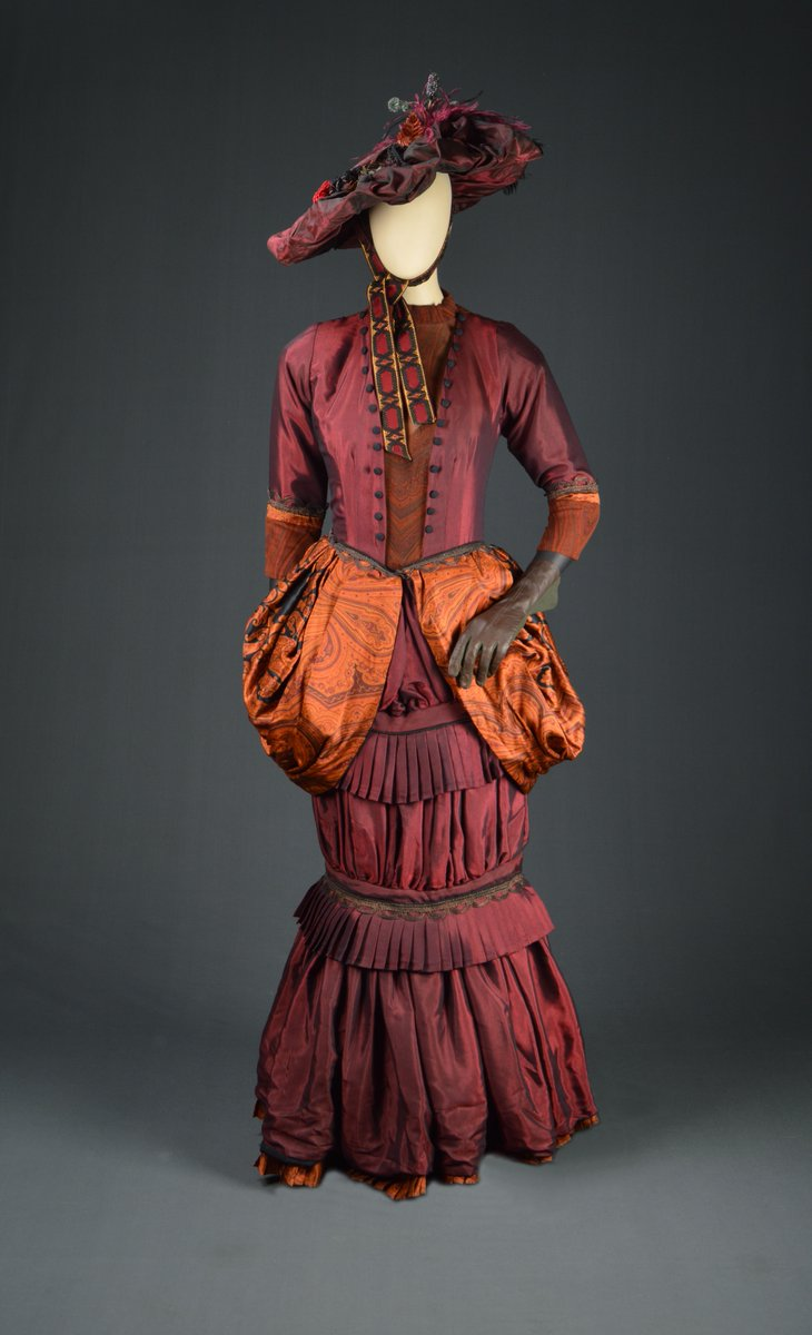 A red taffeta gown with an orange bustle, big hat with bold ribbon. Very narrow around the ankles. Lots of pleating!