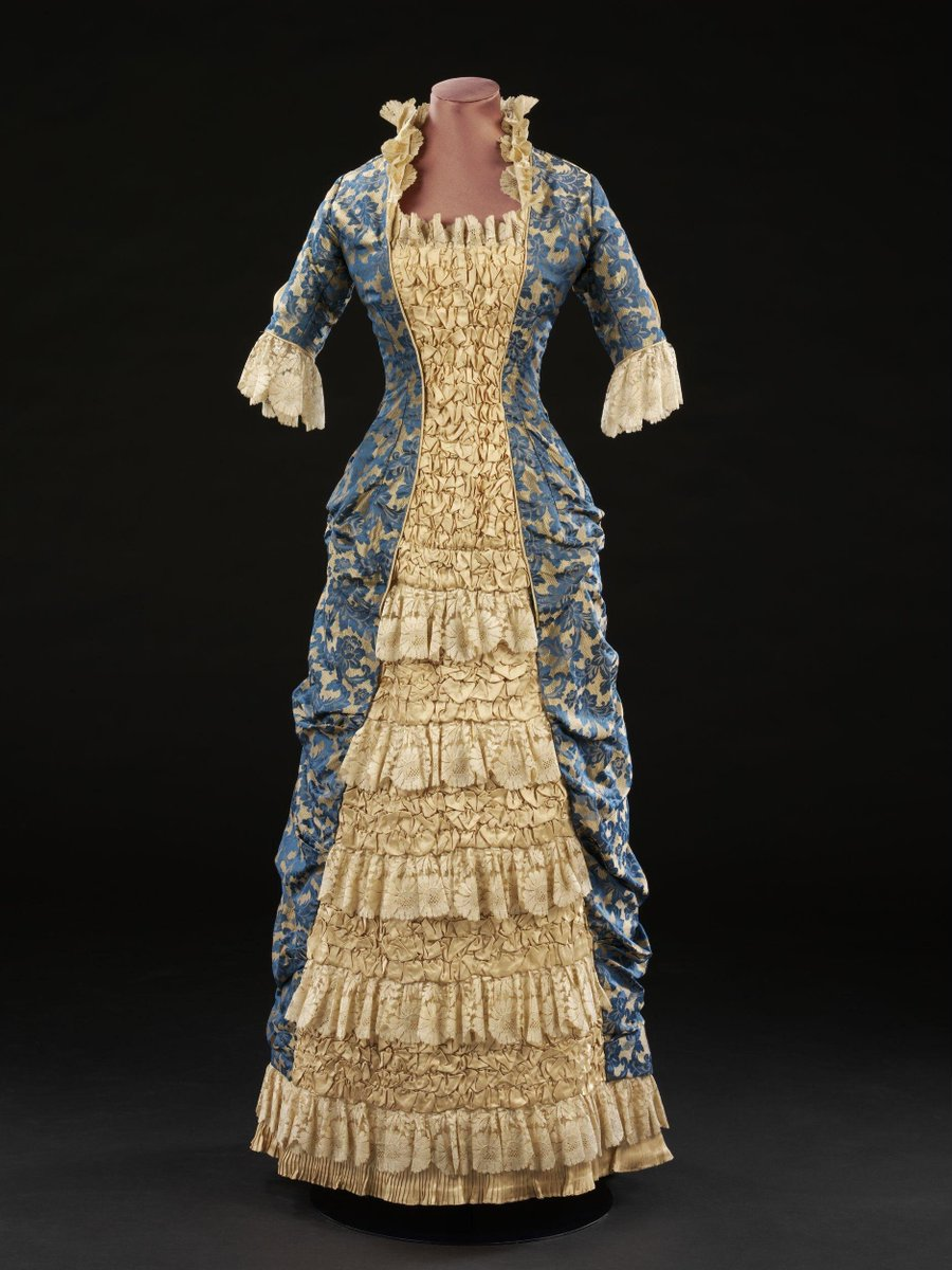 Princess dress of blue and gold Jacquard-woven silk made with a fitted bodice and narrow skirt drawn back into drapes at the back. It has elbow-length sleeves and a square neckline, which are both trimmed with machine-lace. ©Victoria & Albert Museum, London