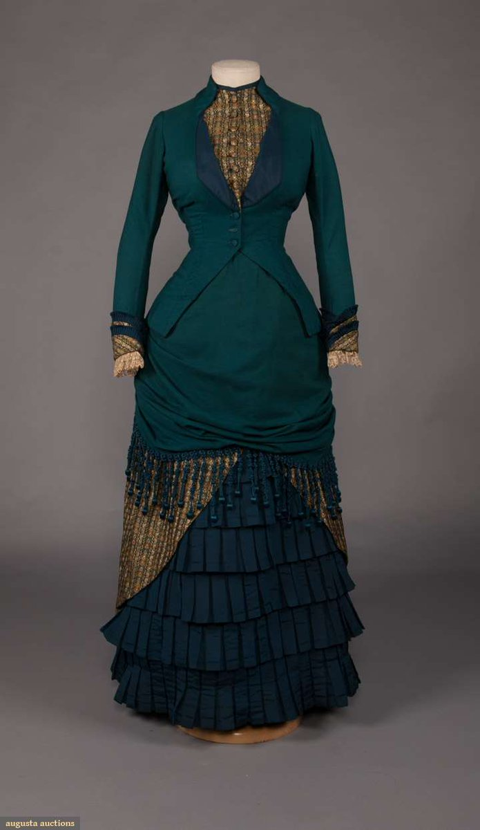 """2-pc teal wool & brocaded silk day dress w/ CF button closure, marine blue corded trim to bustled skirt, B 32"""", W 24"""", Bodice L 19"""", Skirt L 40"""", (few moth holes, spot at left lap, spot stains CB left & to left inner arm, spot at right collar B, small tear to lace at left, missing 1 button on sleeve) good. From Augusta Auctions. 1881."""
