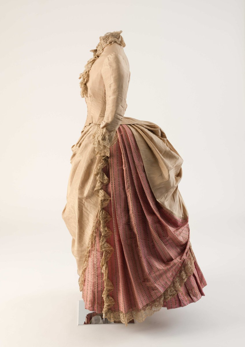 From tweet: Friday Treat Time & a stunning side view of an 1880s bustle! Biscuit and rose-coloured silk day dress with lace trimmings, 1886 -
