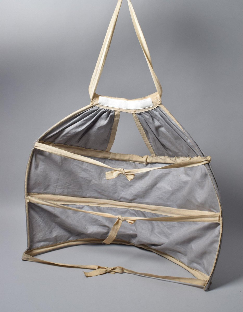 (c)Victoria and Albert Museum, London - A bustle with ties to be worn beneath a dress. The structure is wrapped with material and thicker ribbons to attach to the woman as part of her garment.