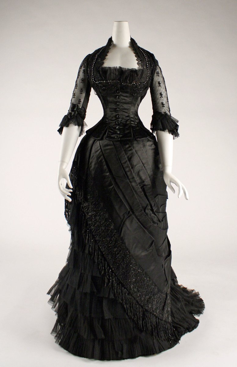 Black satin gown with asymmetrical draping, square neckline, black lace 3/4 length sleeves. Tassels and beadwork at the bottom. Satin buttons down the center.
