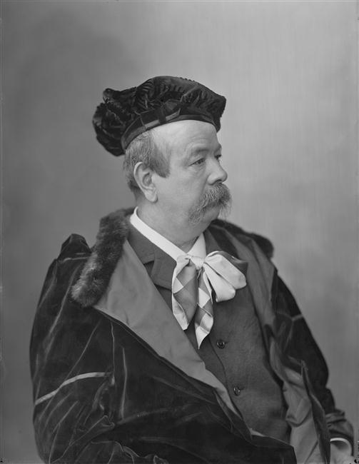 A photograph of Charles Frederick Worth in his later years, draped in fur and velvet, with a silk tie and vest. He wears a velvet beret, has a thick mustache. The image is in black and white and dates from the 1880s. Image: public domain.