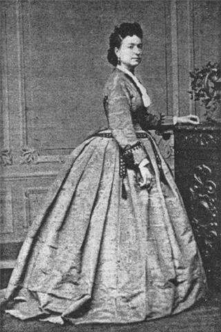 A photograph of a woman standing in a large, Victorian style dress. Black and white. This is likely Marie in one of Worth's early gowns.