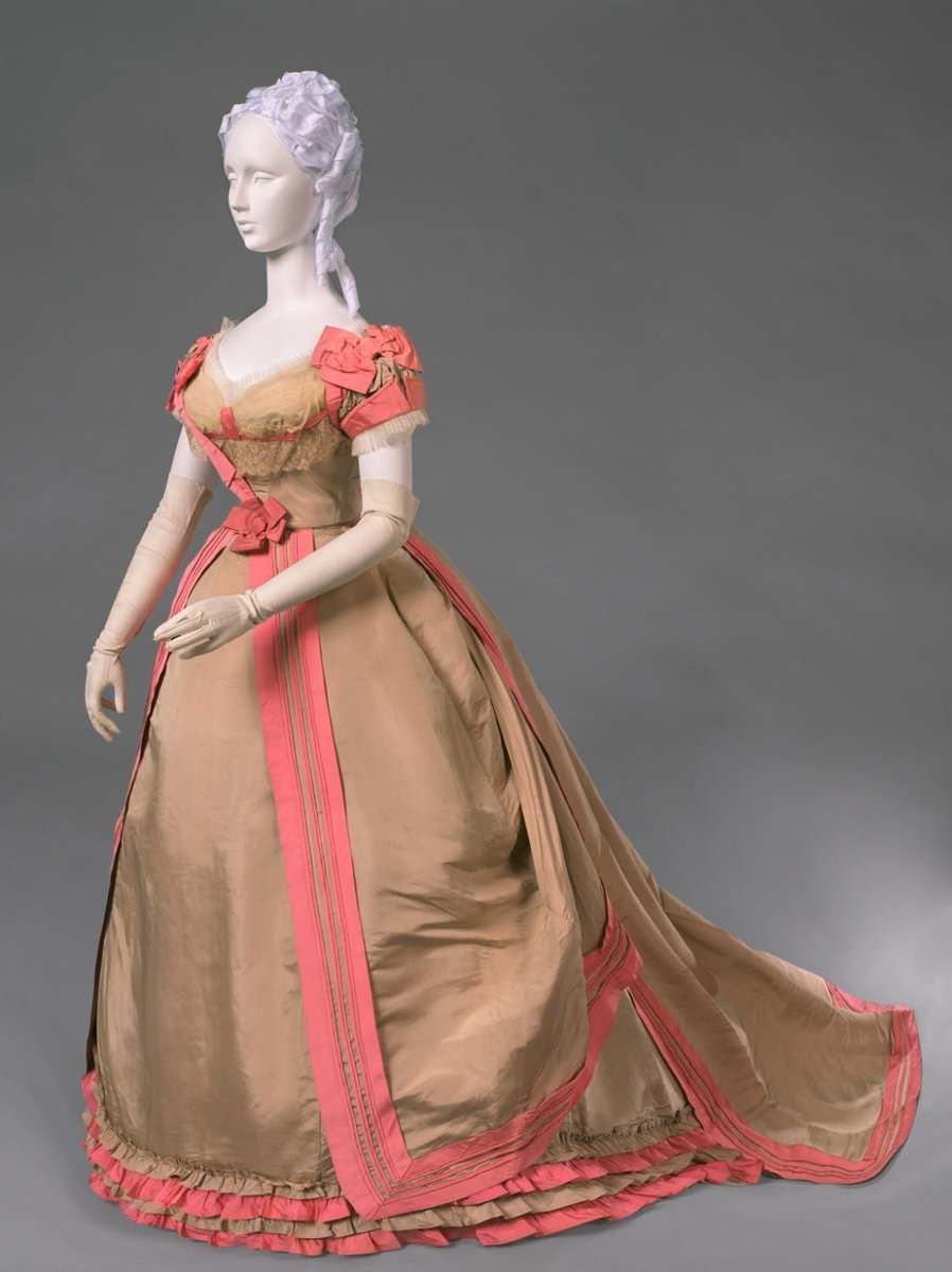 A tan and pink gown, less of a flounce than the last one. The contrasting colors bring to mind porcelain and court colors. There are bows and trim work along the edges, and it's taffeta. So it would make quite the sound when it's on the go. From the Philadelphia Museum of Art.