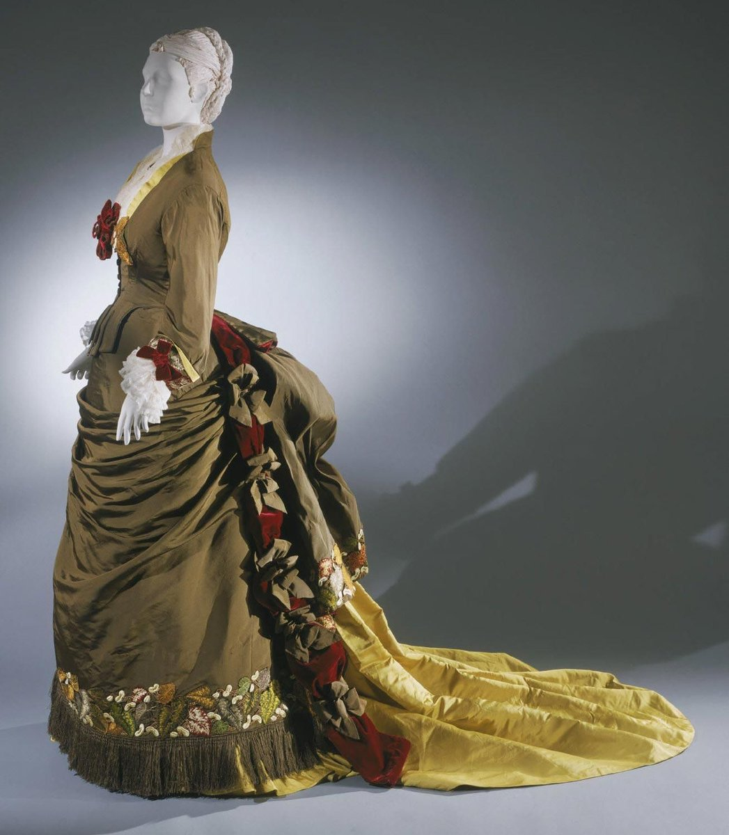 Silk faille with silk satin, silk velvet, embroidered appliqué, sheer pleated silk, silk fringe, and artificial flowers - Chartreuse gown with fringe at the bottom, falls of red roses, and a yellow train. PHL museum of art.