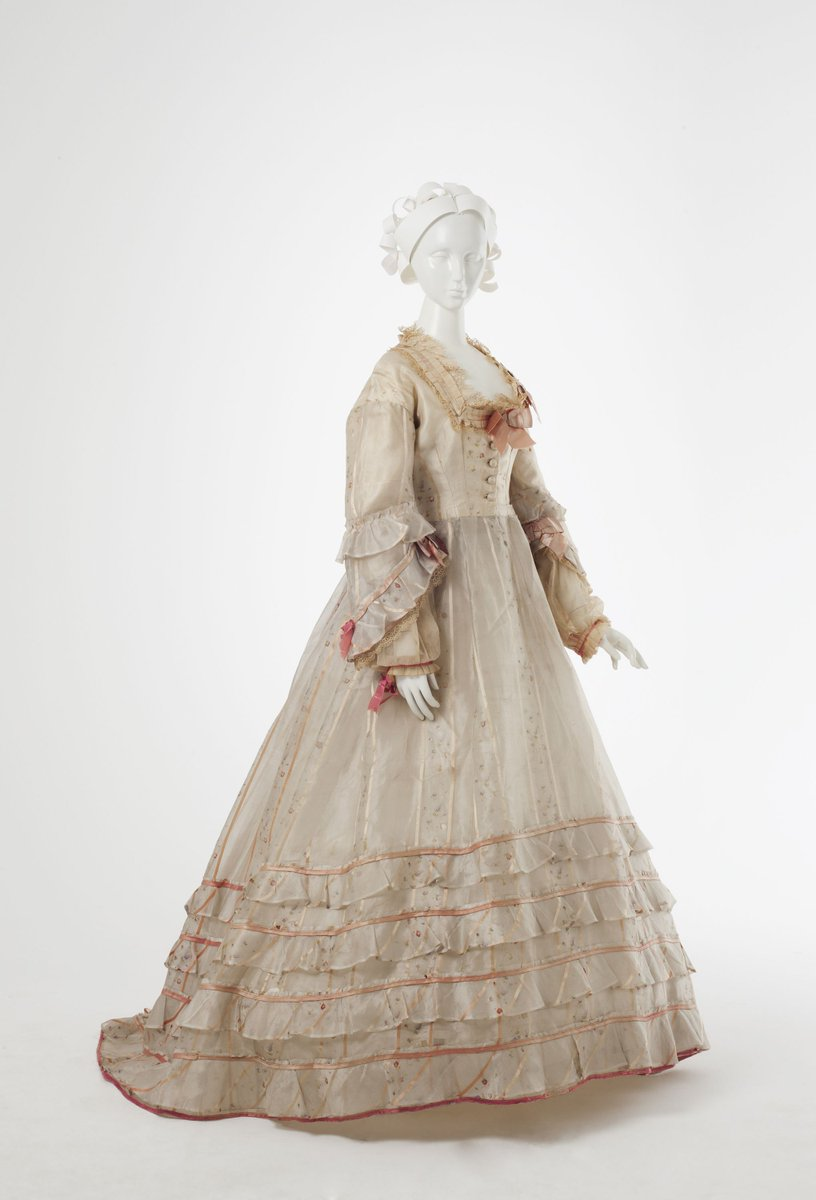 Cream silk voile dress with floral panels & pink stripes. Full, tiered sleeves to elbow & cream net to wrists. Trimmed with rose coloured satin bows at neck & sleeves. Four deep frills on trained skirt. c. 1868.(LC). - MAAS Museum