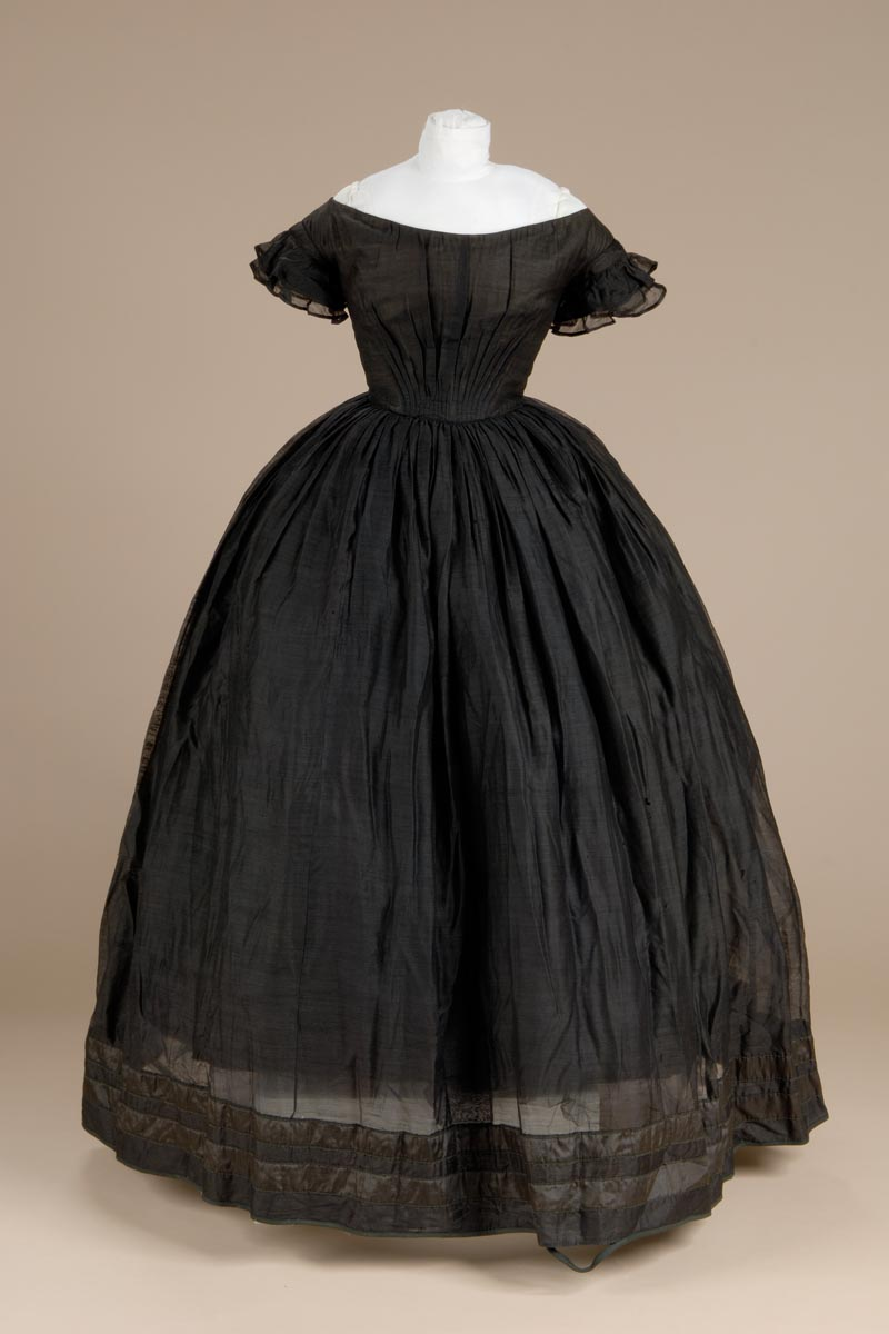 Black mourning dress; thin, almost transparent fabric; short sleeves; top of silk and wool material with two rows of like material sewn on with piping and hemmed at edges; off the shoulder neckline; hook and eyes down back; lined with glazed cotton; pleated at waist in front and back; seven whale bone stays in lining; skirt gathered at waist; bell shaped; bottom bound with black woven tape. The donor of the dress said the garment originally belonged to a woman from Simsbury who attended the Litchfield Female Academy.  Litchfield Historical Society.